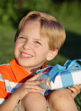 BirthdayBoy. Happy young white boy holding a present outdoors Royalty Free Stock Image