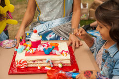 Birthdays cake. Happy little girl is celebrating her birthday with cake outside in the park stock images