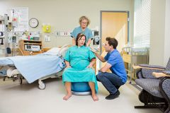 Birthing Mother Having Contraction. Mature nurse and men consoling pregnant women undergoing a contraction sitting on exercise ball in hospital royalty free stock images