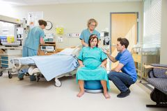 Birthing Mother in Hospital having Contraction. Nurse and men consoling pregnant women sitting on fitness ball in hospital royalty free stock images