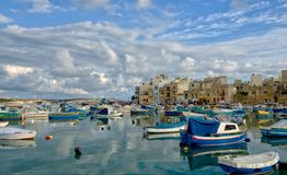 Birzebugga, MALTA-Aug 29: traditional Maltese fishing boats with reflection in maltese village Birzebugga, MALTA in Aug 29,2016. Birzebugga, MALTA-Aug 29 Royalty Free Stock Photography