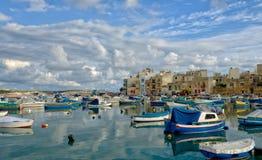 Birzebugga, MALTA-Aug 29: traditional Maltese fishing boats with reflection in maltese village Birzebugga, MALTA in Aug 29,2016. Royalty Free Stock Photography