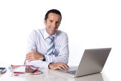 40 bis 50 Jahre alte ältere Geschäftsmann, die an Computer am Schreibtisch schaut überzeugt und entspannt arbeiten Stockfotografie