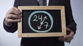 24 bis 7 zeichnend auf Tafel, Geschäftsmann, der Zeichen, Geschäftszeitkonzept hält stock video footage