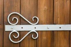 Bisagra forjada blanca puesta en el primer de madera de la puerta foto de archivo