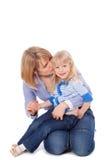 Bisbiglio della mamma in orecchio del bambino Immagine Stock