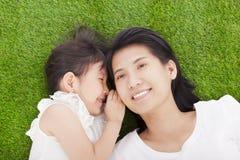 Bisbolhetice de sussurro da mãe e da filha na grama Foto de Stock Royalty Free