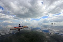 Woman kayaking in Biscayne National Park, Florida. Biscayne National Park, Florida 01-25-2014 Woman kayaks on a very calm Biscayne Bay amidst a dramatic stock images