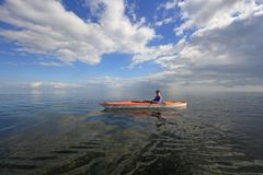 Woman kayaking in Biscayne National Park, Florida. Biscayne National Park, Florida 01-25-2014 Woman kayaks on a very calm Biscayne Bay amidst a dramatic royalty free stock image