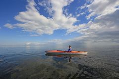 Woman kayaking in Biscayne National Park, Florida. Biscayne National Park, Florida 01-25-2014 Woman kayaks on a very calm Biscayne Bay amidst a dramatic stock photography