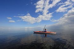 Woman kayaking in Biscayne National Park, Florida. Biscayne National Park, Florida 01-25-2014 Woman kayaks on a very calm Biscayne Bay amidst a dramatic royalty free stock photo