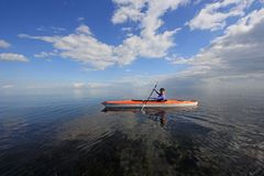 Woman kayaking in Biscayne National Park, Florida. Biscayne National Park, Florida 01-25-2014 Woman kayaks on a very calm Biscayne Bay amidst a dramatic royalty free stock photos