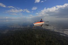 Woman kayaking in Biscayne National Park, Florida. Biscayne National Park, Florida 01-25-2014 Woman kayaks on a very calm Biscayne Bay amidst a dramatic royalty free stock photography