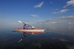 Woman kayaking in Biscayne National Park, Florida. Biscayne National Park, Florida 01-25-2014 Woman kayaks on a very calm Biscayne Bay amidst a dramatic royalty free stock images