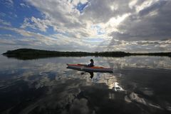 Woman kayaking in Biscayne National Park, Florida. Biscayne National Park, Florida 01-25-2014 Woman kayaks on a very calm Biscayne Bay amidst a dramatic stock photos