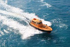 Biscayne Pilot Boat. Top shot of the Biscayne Pilot Boat sailing on the Miami, Florida ocean waters. A pilot boat pulls alongside a cruise ship. A pilot boat is royalty free stock photos