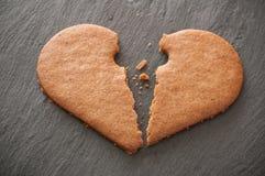 biscoito dado forma do coração quebrado no fundo do quadro Fotografia de Stock Royalty Free