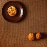 Biscoito em uma placa Porcas em um fundo marrom Fotos de Stock Royalty Free