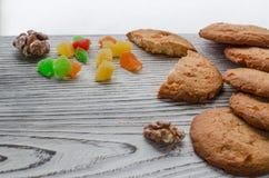 Biscoitos alaranjados redondos com frutos cristalizados coloridos e uma fatia de laranja suculenta que encontra-se em uma tabela  fotos de stock