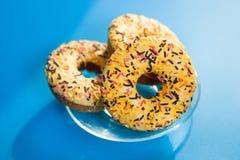 Biscoitos amarelos bonitos dos anéis de espuma no fundo azul com luz do sol, alimento insalubre foto de stock royalty free