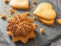 Biscoitos amarelos do gengibre na forma dos flocos de neve e dos corações sobre Fotos de Stock Royalty Free