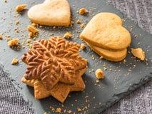 Biscoitos amarelos do gengibre na forma dos flocos de neve e dos corações sobre Imagens de Stock Royalty Free