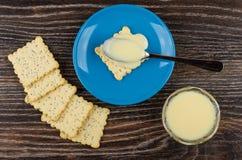 Biscoitos, bacia com leite condensado, colher com leite em uns pires fotografia de stock