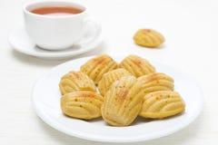 Biscoitos caseiros de madeleine e um copo do chá Fotos de Stock Royalty Free
