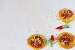 Biscoitos caseiros numa forma da pizza em um fundo abstrato branco com pimentas e alecrins de pimentão Espaço para o texto Imagens de Stock