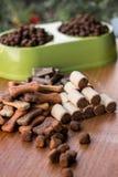 Biscoitos coloridos saborosos do cão no fundo de madeira imagem de stock royalty free