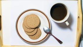 Biscoitos de Brown no prato que emparelha-se com o café preto com colher de chá Imagens de Stock Royalty Free