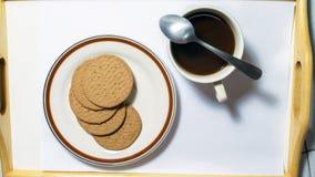 Biscoitos de Brown no prato que emparelha-se com o café preto com colher de chá Fotos de Stock
