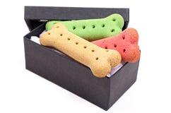 Biscoitos de cão dentro de uma caixa negra Fotografia de Stock Royalty Free
