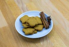 Biscoitos do gengibre em uma placa branca com varas e anis de canela Imagens de Stock