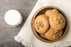 Biscoitos do mel com um núcleo da noz em uma bacia de madeira em um guardanapo claro Biscoitos com leite fotografia de stock