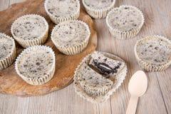 Biscoitos e bolos de queijo de creme em formulários do queque imagem de stock