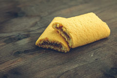 Biscoitos, enchidos com o doce com as cerejas no fundo de madeira da tabela Fotografia de Stock