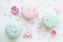 Biscoitos franceses tradicionais da sobremesa dos bolinhos de amêndoa do arando da morango do mirtilo com arranjo de flores bonit Fotografia de Stock