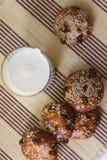 Biscoitos na tabela com sementes de sésamo, passas e um vidro do leite jogo Fotografia de Stock Royalty Free