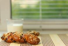 Biscoitos na tabela com sementes de sésamo, passas e um vidro do leite No janela-peitoril Comer saudável Imagens de Stock