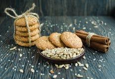 Biscoitos saborosos no cereal e na canela no fundo de madeira Foto de Stock Royalty Free