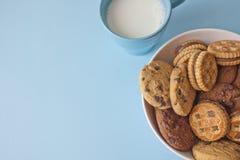 Biscoitos sortidos na bacia com leite do copo Fotografia de Stock