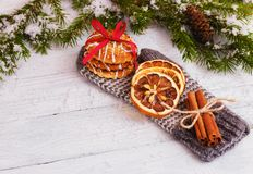 Biscoits, orange, cinnamon sticks on glove. wooden background. Christmas concept royalty free stock photo