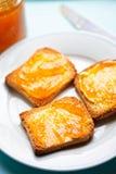 Biscotte avec de la confiture d'abricot sur la surface bleue image libre de droits