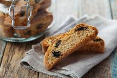 Biscotti或cantucci用葡萄干在木土气桌,传统意大利饼干上 图库摄影