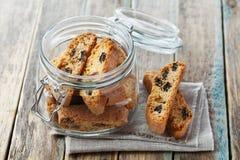 Biscotti或cantucci用葡萄干在木土气桌,传统意大利饼干上 免版税库存图片