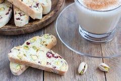 Biscotti用蔓越桔和开心果,咖啡拿铁 免版税库存照片