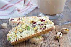 Biscotti με το το βακκίνιο και φυστίκι με το φλιτζάνι του καφέ latte Στοκ Φωτογραφίες