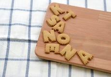 Biscotti ABC sul piatto di legno Fotografie Stock