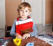 Biscotti adorabili del pane dello zenzero di cottura del ragazzo per il Natale Immagine Stock Libera da Diritti